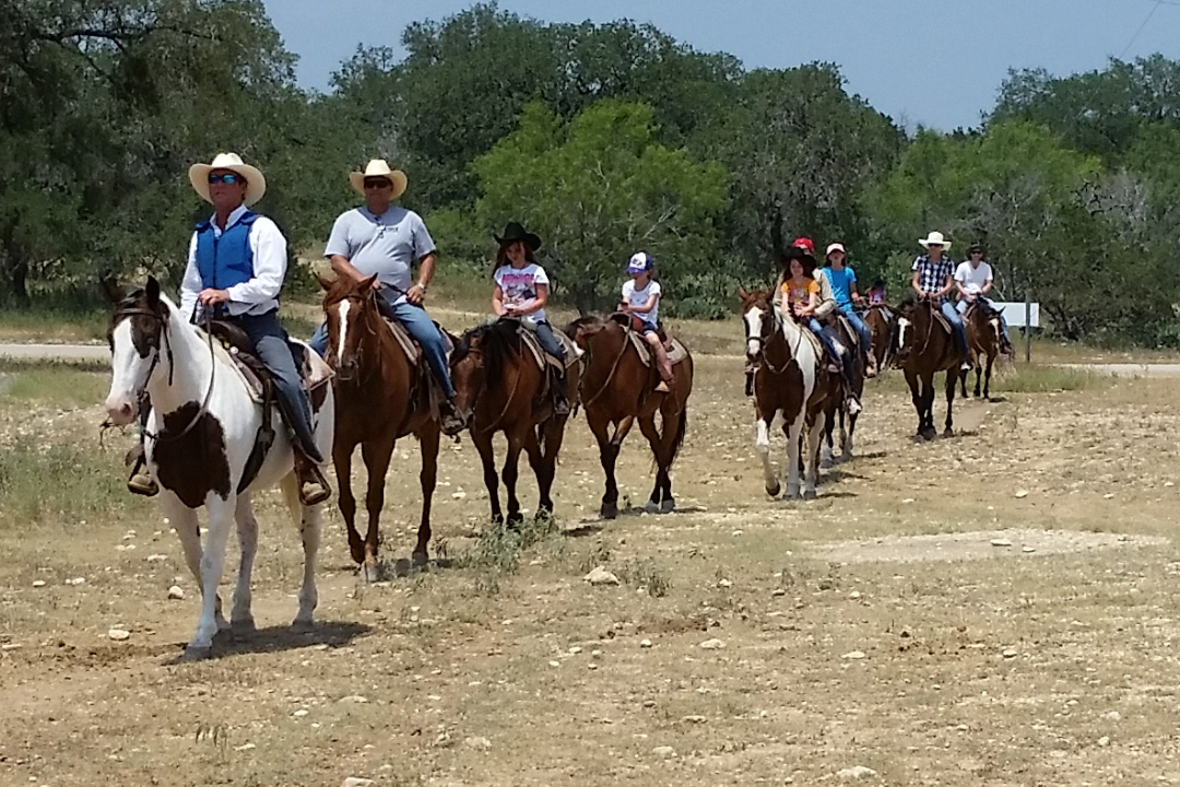 Man wearing a Cool58 phase change cooling vest on horseback while leading a group of people on horses