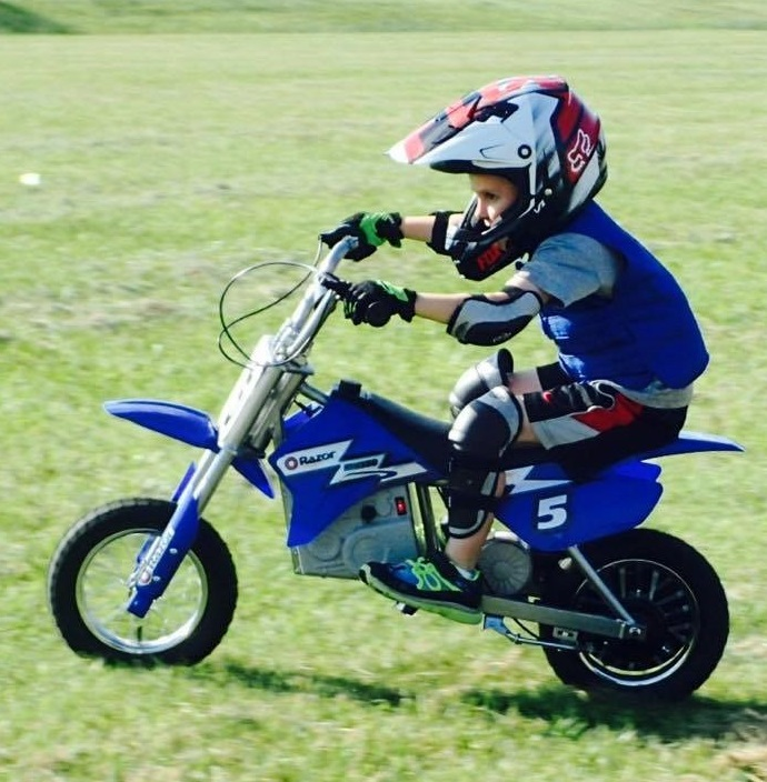 Boy wearing a blue Cool Kids cooling vest on a dirt bike