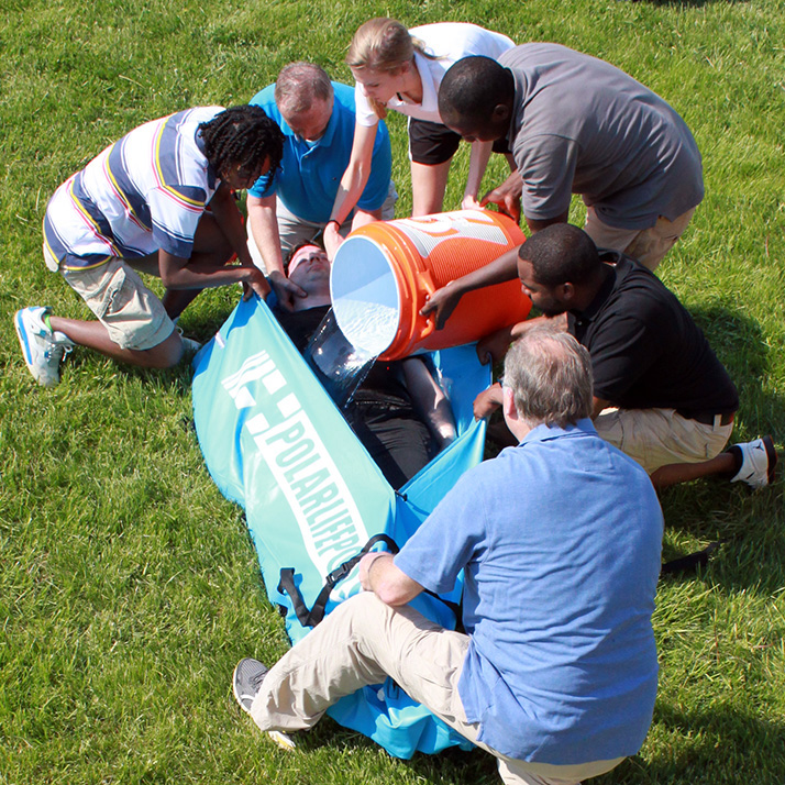 Group of people pouring water on a man in a polar life pod cold water immersion device