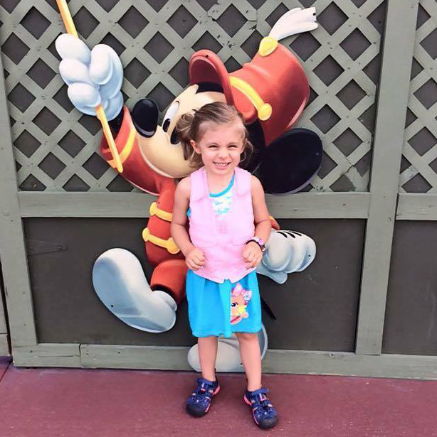 Girl in pink kool max toddler cooling vest standing in front of a picture of Mickey Mouse