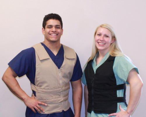 Man in scrubs wearing a khaki kool max zipper front vest and woman in scrubs wearing a black kool max zipper front vest